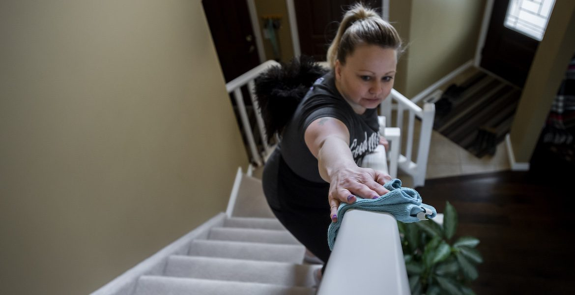 worker green cleaning a stair banister