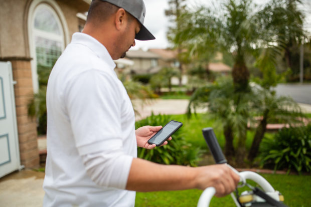 Image of pool service professional using field service management software