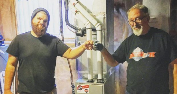 Two HVAC techs fist bump in front of a finished furnace install
