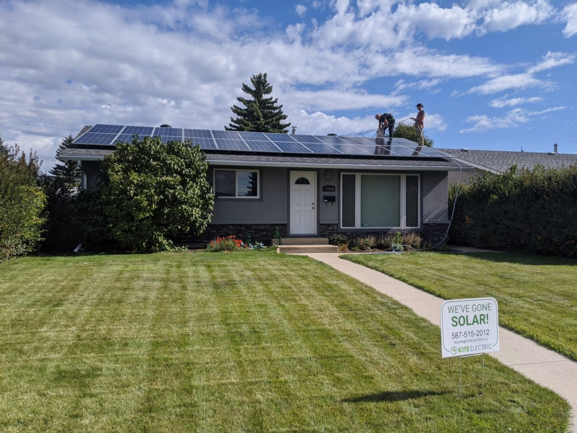 Electrical contractors on roof installing solar panels