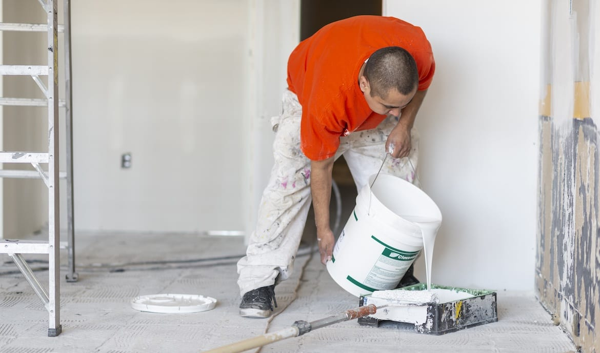 Handyman pouring paint into a tray