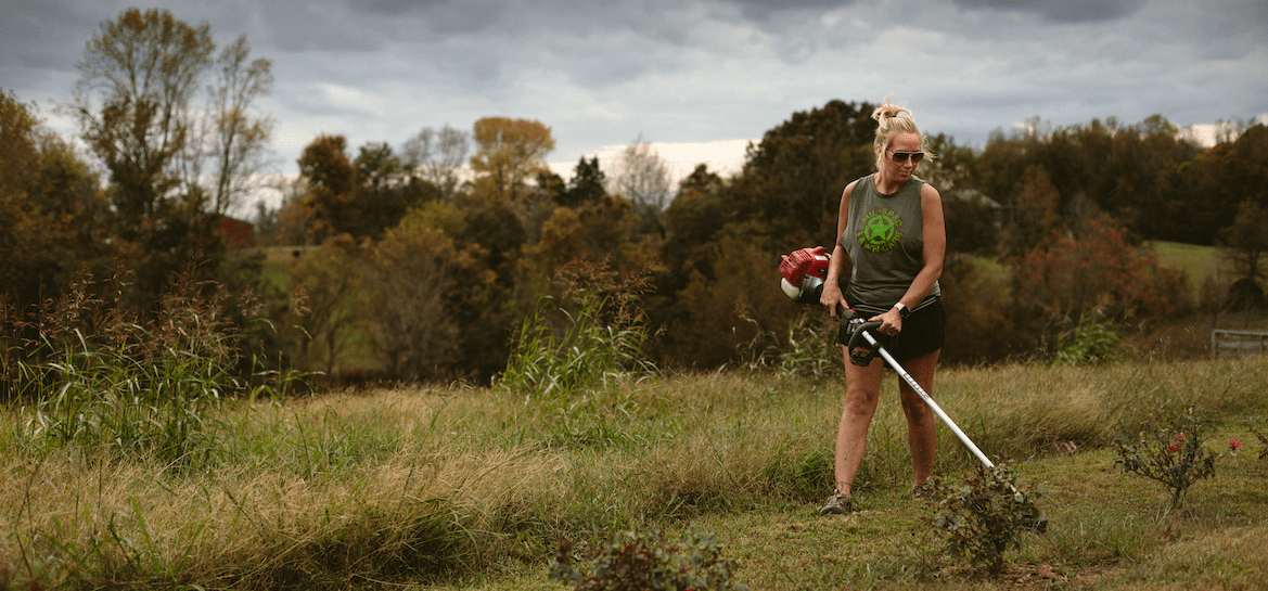 Lawn care professional using a weed whacker on a lawn