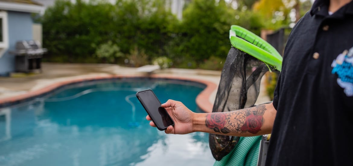 Worker holding phone near pool and cleaning equipment